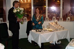 Mark presents Janet with flowers.